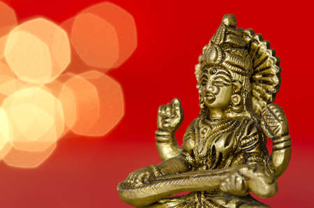 saraswati: close up of a Hindu deity statue with lights in the back on red background