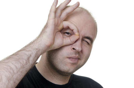 monocle: young man looking through his fingers like monocle on white background