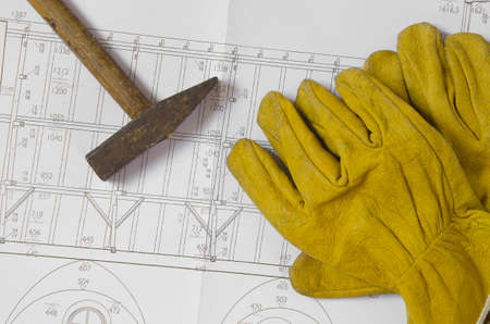 building plans with hammer and working gloves on top photo