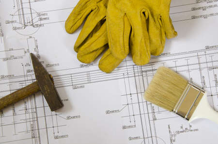 building plans with hammer, paint brush and working gloves on top photo
