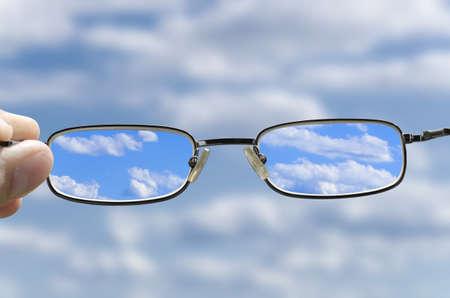 フォーカス、視力矯正メガネを持っている手を空から