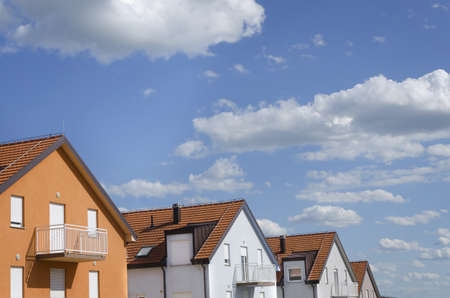 roofs of houses in different colors under blue sky with clouds above photo