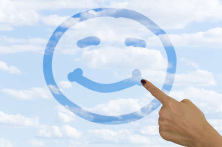hand drawing a smiley face on a foggy window with a finger revealing clear blue sky on the other side Stock Photo - 21541033