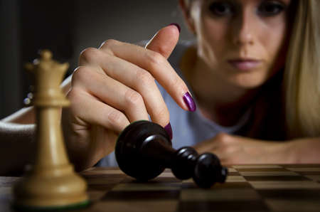 abandoning: woman surrendering her king after loosing a game of chess