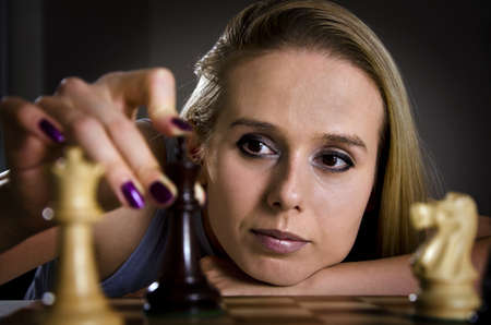 woman playing chess making her move with focus on the eyes of a woman photo