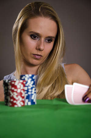 strategizing: woman playing poker lifting her cards thinking about the game