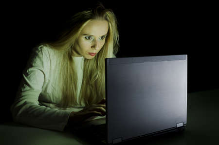 woman working on a computer by night in a dark room with only light from computer falling on her face horizontally cropped