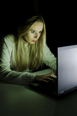 woman working on a computer by night in a dark room with only light from computer falling on her face vertically cropped