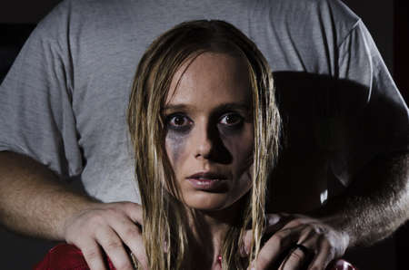 portrait of an abused woman with untidy hair and smudged makeup with a man standing behind her holding his hands on her shoulders cropped horizontally photo