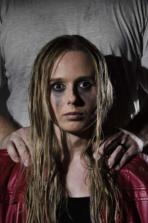 portrait of an abused woman with untidy hair and smudged makeup with a man standing behind her holding his hands on her shoulders cropped vertically photo