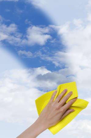 cleaning window: Finestra di pulizia a mano rendendo pi� facile vedere cielo blu attraverso essa ritagliata verticalmente