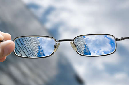 blurred vision: out of focus glass business building with sky and clouds above and hand holding glasses that correct the vision Stock Photo