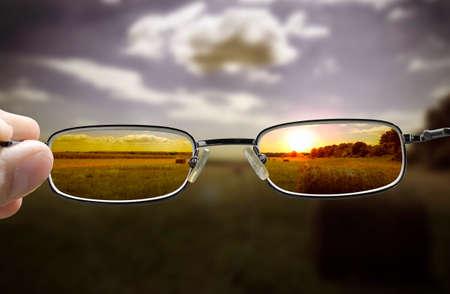 夕暮れ時、視力矯正メガネを持っている手にフォーカス自然から