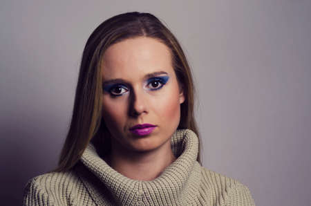 fashion portrait of a blonde woman in studio wearing a heavy make up and a turtleneck sweater photo