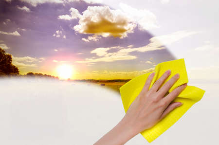 fenêtre de nettoyage à la main ce qui rend plus facile de voir le coucher du soleil
