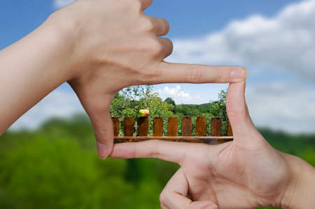 out of focus empty nature landscape and fingers creating a square making the vision of the future clear Stock Photo
