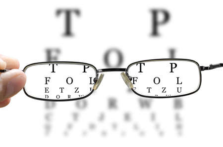 blurred vision: out of focus eye test and a hand holding glasses correcting the vision horizontal Stock Photo