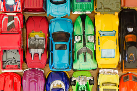 car lots: lots of miniature cars in different colors on a wooden floor background