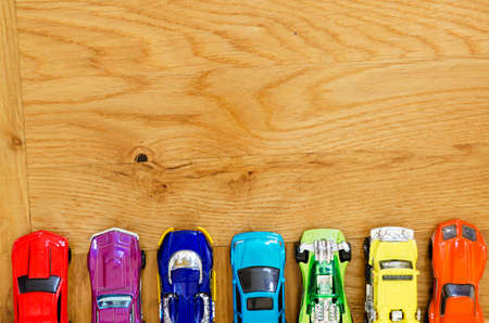 miniature cars in different colors lined up on a wooden floor