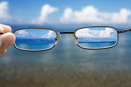 blurred vision: blurry vision of a seashore on a beautiful summer day and a hand holding a pair of glasses that correct the vision
