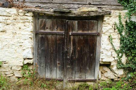 worn: old worn out wooden door with rusty metal hinges