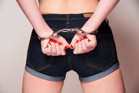 handcuffs: sexy woman wearing denim shorts with hands clenched in fists wearing a pair of handcuffs