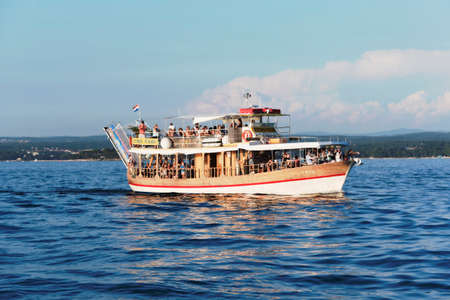 acquired: Porec, Croatia - Circa 2016: Tourist ship taking people sightseeing off the coast of Porec, Croatia. A spot on the tourist ship can be acquired in most bigger towns along the Croatian coastline