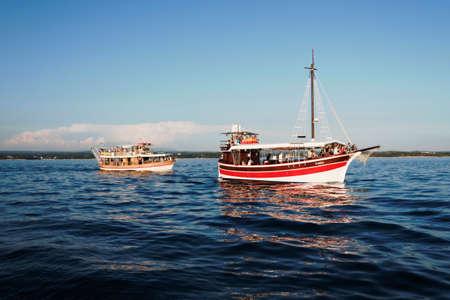 acquired: Porec, Croatia - Circa 2016: Tourist ships taking people sightseeing off the coast of Porec, Croatia. A spot on the tourist ship can be acquired in most bigger towns along the Croatian coastline