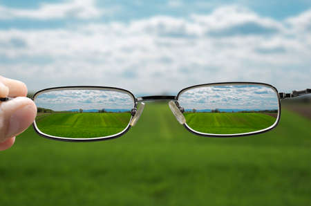 shortsighted: out of focus nature with farmlands and a hand holding a glasses that correct the vision