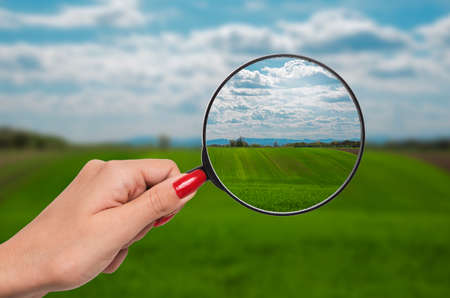 shortsighted: out of focus nature with farmlands and a hand holding a magnifying glass that correct the vision