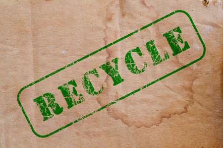 groene recycle stempel op een stuk oud bruin gekleurd karton Stockfoto