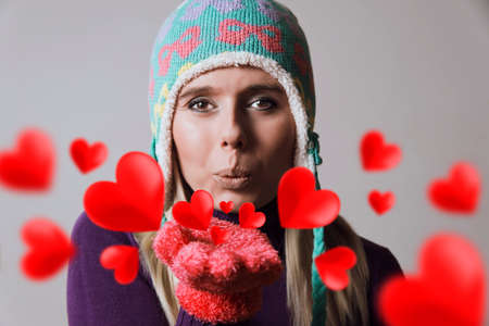 beautiful blonde woman wearing winter clothing blowing heart kisses Stock Photo