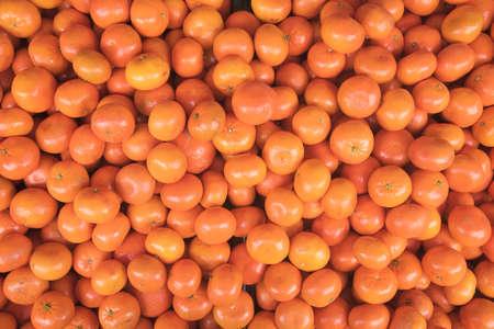 lots of fresh mandarin oranges forming an orange background