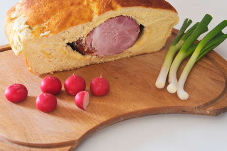 ham in a bread on a cutting board along with radishes and spring onions Stock Photo - 99858795