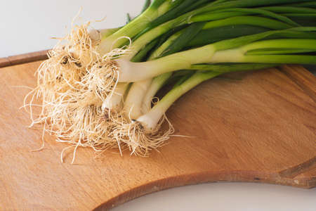 pile of fresh green spring onions on a cutting board