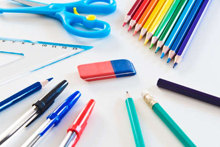 Different Kind of Colorful School and Office Utensils Arranged on a White Surface