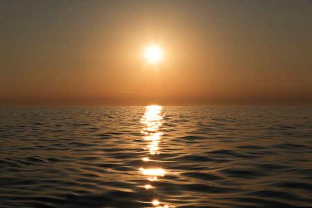 fading sun in the dusk over calm sea