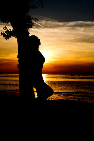 silhouette of a woman leaning on a tree enjoying sunset on a beach
