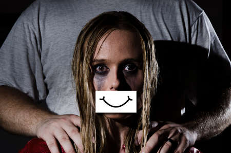 concept abused woman with gauged mouth and a fake smile hiding the abuse and a man standing behind her with his hands on her shoulders Reklamní fotografie