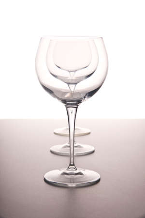 clear clean transparent wine glasses in a row on a white background