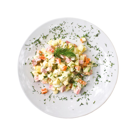 Olivier salad on a plate, isolated on white background. Top view Stock Photo