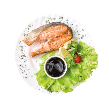 Baked piece of fish, lettuce and sauce on the plate, isolated on white background. Top view Reklamní fotografie