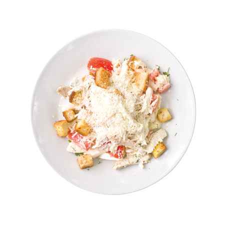 Caesar salad with chicken on the plate, isolated on white background. Top view