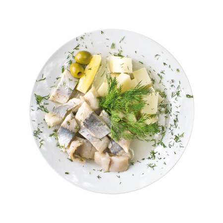 Pieces of herring, potatoes and leaf lettuce on a plate, isolated on white background. Top view