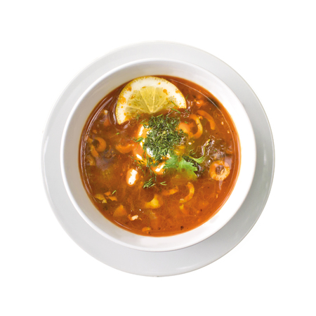 Solyanka soup in the plate, isolated on white background. Top view