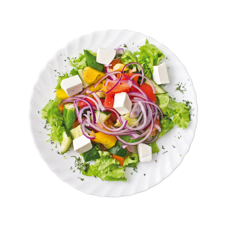 Greek Salad on a plate, isolated on white background. Top view.