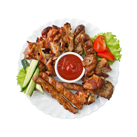 Grilled meat, sausages and tomato sauce on the plate, isolated. Top view