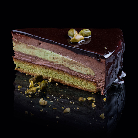 Pistachio biscuit with chocolate cream-mousse on a black background