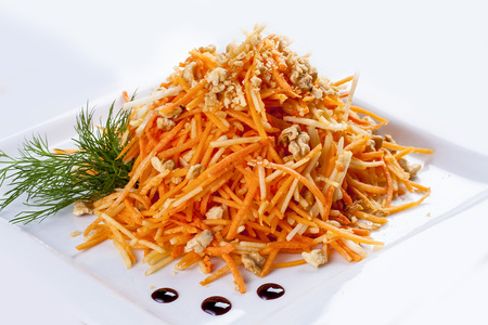 Grated carrots with walnuts. On a white plate. Banco de Imagens