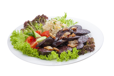 Blood sausage with vegetables and salad. On a white plate